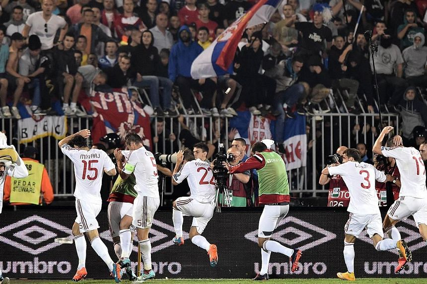 Albania's players run for cover during the EURO 2016 group I football match between Serbia and Albania in Belgrade on Oct 14, 2014.A chunk of concrete, stones, coins and lighters were hurled at Albania's players and officials before and during