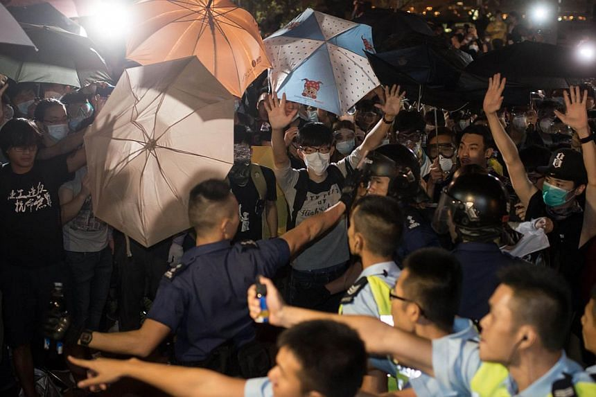 Pro-democracy protesters clash with police outside the central government offices in the Admiralty district of Hong Kong, on Oct 15, 2014. -- PHOTO: AFP