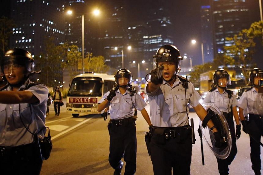 A police officer yells at protesters to move away from the road as they try to block an area near the government headquarters building in Hong Kong, Oct 15, 2014. -- PHOTO: REUTERS