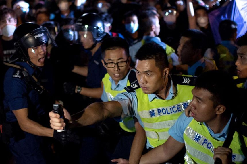 A police officer threatens to use pepper spray on a crowd of pro-democracy protesters in Hong Kong, on Oct 16, 2014. -- PHOTO: AFP