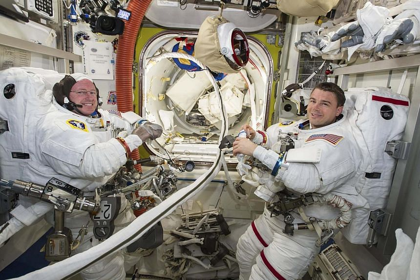 Nasa astronauts Reid Wiseman (right) and Barry Wilmore work inside the International Space Station on Oct 1, 2014. The two spacewalking Nasa astronauts hustled and muscled through an electrical repair job outside the International Space Station on Oc
