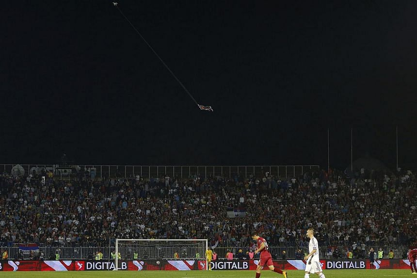 """Tuesday's Serbia-Albania Euro 2016 qualifier - at which Albanian fans were barred due to tensions between the two countries - was called off when a remote-controlled plane flew a the flag of """"Greater Albania"""" above the field (above), sparking a brawl"""