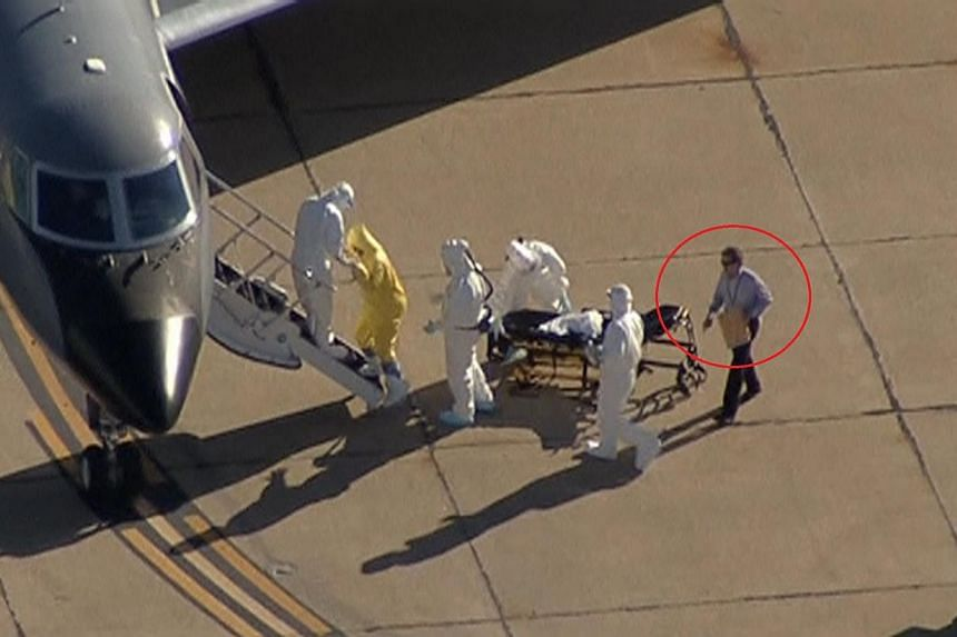 """A screenshot shows """"Clipboard Man"""" (circled) directing operations as nurseAmber Vinson, the second health-care worker to have become infected after treating Liberian patientThomas Eric Duncan, is moved from Dallas to Atlanta. -- SCREENGRA"""