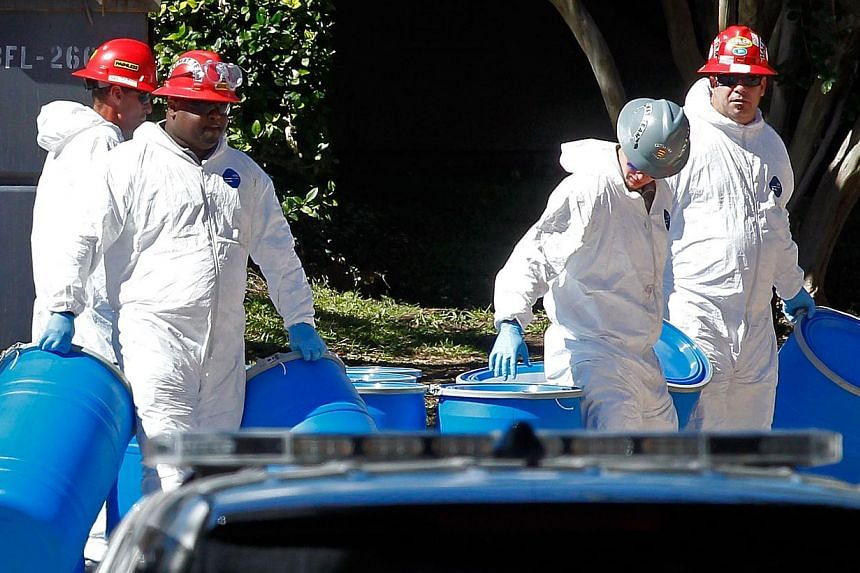 Hazmat workers with Protect Environmental unload barrels in preparation for decontaminating an apartment at The Village Bend East apartment complex where a second health-care worker who has tested positive for the Ebola virus resides on Oct 15, 2014