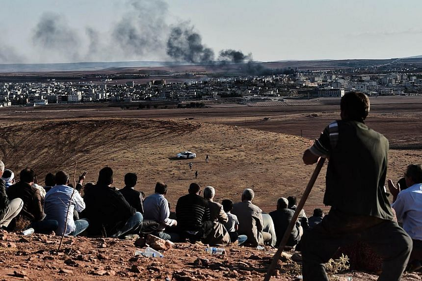Kurdish people watch smoke billowing from Kobane as they gather upon a hill overlooking the Syrian town of Kobane, also known as Ain al-Arab, in the southeastern village of Mursitpinar, Sanliurfa province, on Oct 15, 2014. US-led airstrikes have kill