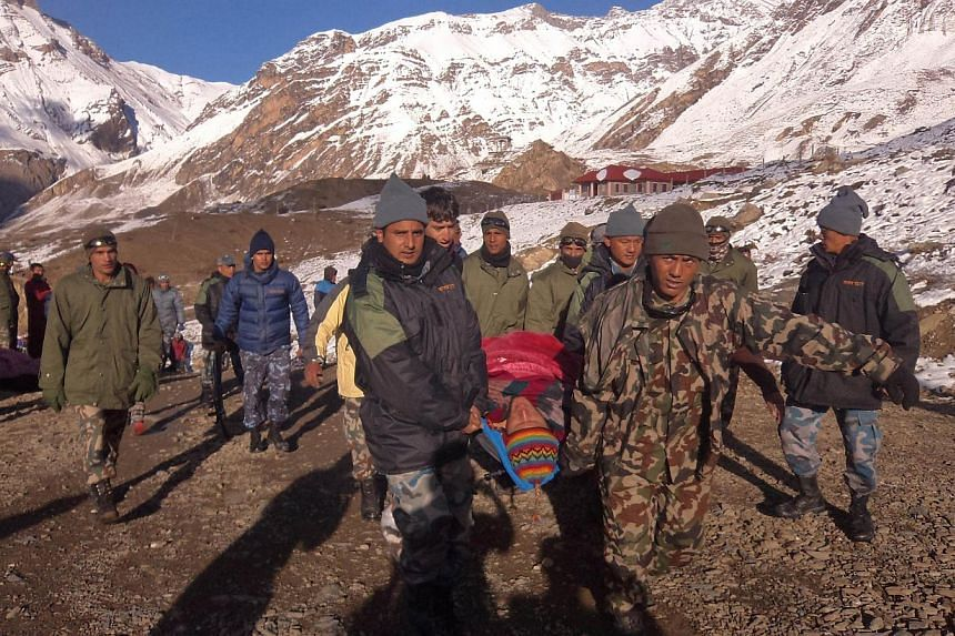 In this handout photograph released by the Nepal Army on Oct 15, 2014, an injured survivor of a snow storm is assisted by Nepal Army personel in Manang District, along the Annapurna Circuit Trek. A snowstorm and avalanche in Nepal's Himalayas has kil
