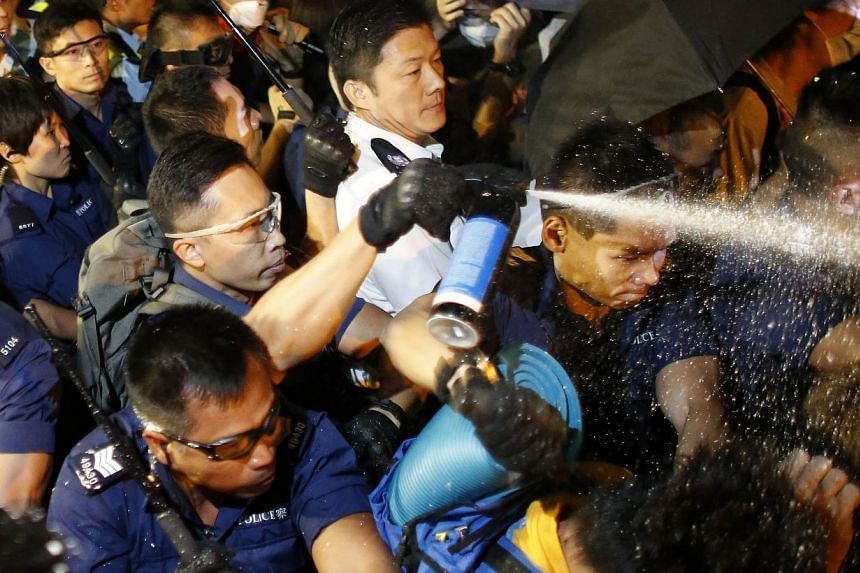 Police use pepper spray as they clash with pro-democracy protesters at an area near the government headquarters building in Hong Kong early Oct 16, 2014. Hong Kong's justice chief insisted Wednesday that any prosecution of plain-clothes officers wh
