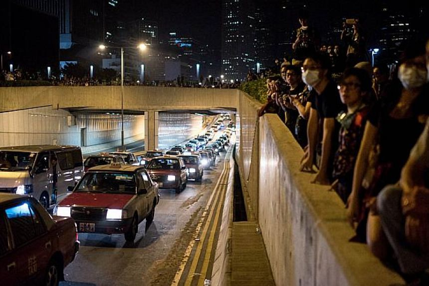 Pro-democracy protesters look over a major road they had sought to occupy but were pushed back by police in Hong Kong on Oct 16, 2014. Hong Kong's justice chief insisted Wednesday that any prosecution of plain-clothes officers who were filmed beati