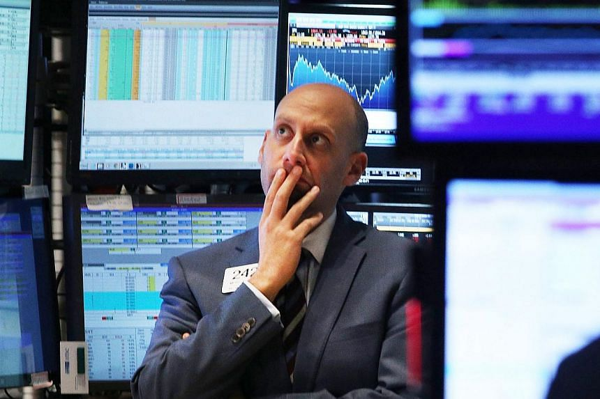 A trader works on the floor of the New York Stock Exchange on Oct 15, 2014 in New York City. As fears from Ebola and a global slowdown spread, stocks plunged on Wednesday with the Dow falling over 400 points during the afternoon before receovering sl