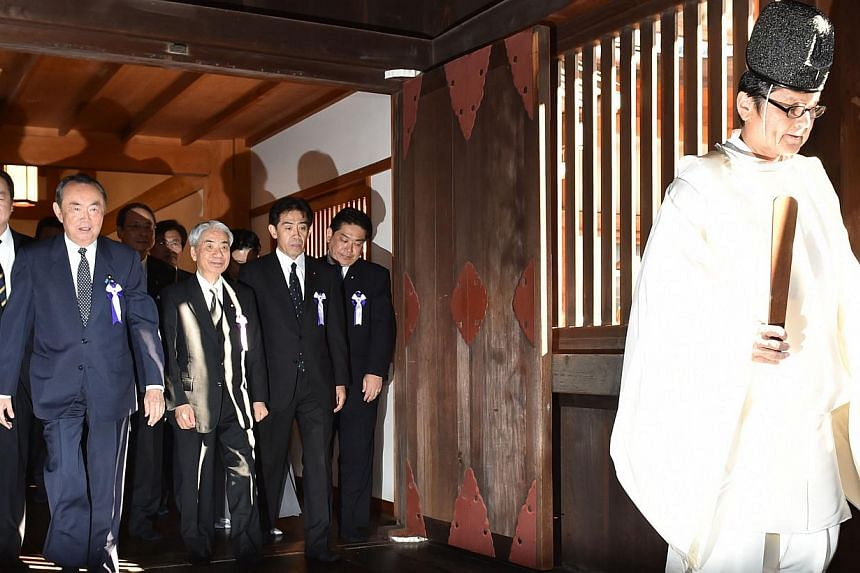 Japanese lawmakers follow a Shinto priest (right) during a visit to the controversial Yasukuni shrine on Oct 17, 2014. -- PHOTO: AFP
