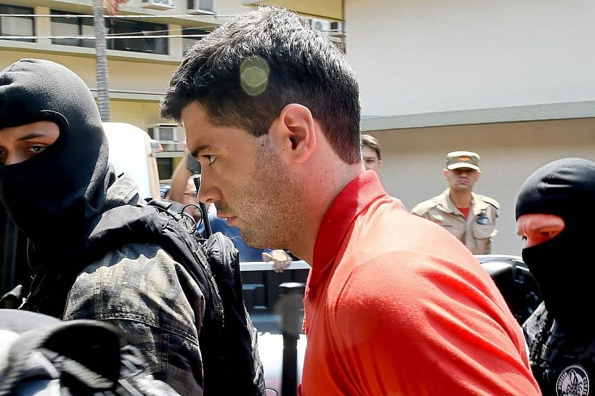 Alleged serial killer Thiago Henrique Gomes da Rocha(centre), suspected of killing 39 people, is escorted by police officers at the Department of Security, a day after his arrest, in Goiania, state of Goias, Brazil, on Oct 16, 2014. -- PHOTO: A
