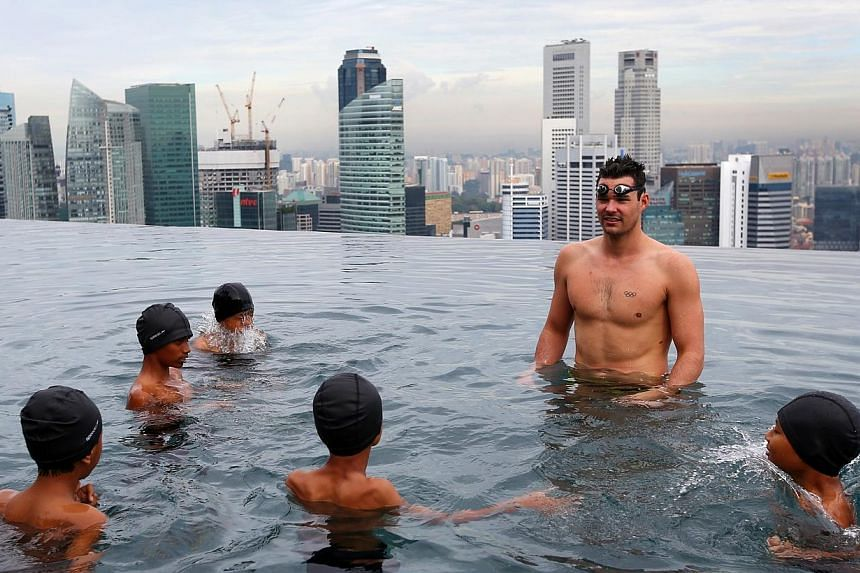 World 100m breaststroke champion Christian Sprenger at the Marina Bay Sands' infinity pool on May 20, 2014, where he conducted a short swimming clinic for youth from SportCares Foundation and Sands for Singapore. -- ST PHOTO: GARY GOH