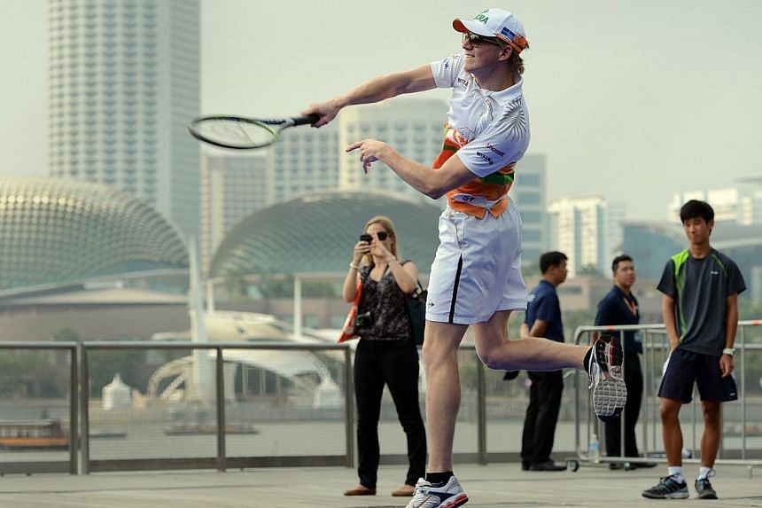 Force India's Formula One (F1) driver Nico Hulkenberg hitting an ungainly shot as he plays a game of tennis with a fellow F1 driver and professional tennis stars at the Event Plaza at Marina Bay Sands on Sept 20, 2012. -- ST PHOTO: JOYCE FANG