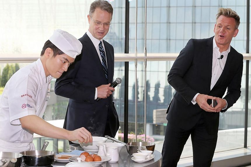 Gordon Ramsay (right), British celebrity chef, watching Tay Yi Wen of At-Sunrice cooking eggs during the cook-off competition at Marina Bay Sands (MBS) where chefs had 10 minutes to cook eggs three ways: poached, soft-boiled and omelette. -- ST PHOTO
