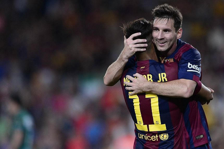 Barcelona's Neymar is congratulated by his teammate Lionel Messi on Aug 18, 2014. -- PHOTO: AFP