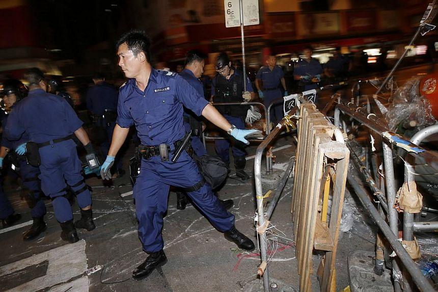 A policeman removes a barricade at a protest site at Mongkok shopping district in Hong Kong October 17, 2014. -- PHOTO: REUTERS