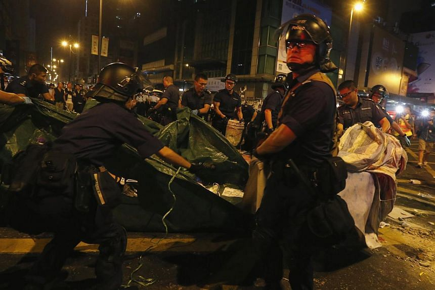 Police demolish a tent on a road blocked by pro-democracy protesters at the Mong Kok shopping district in Hong Kong, on Oct 17, 2014. -- PHOTO: REUTERS