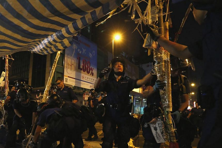 Police take down a tent on a road blocked by pro-democracy protesters at the Mong Kok shopping district in Hong Kong, on Oct 17, 2014. -- PHOTO: REUTERS