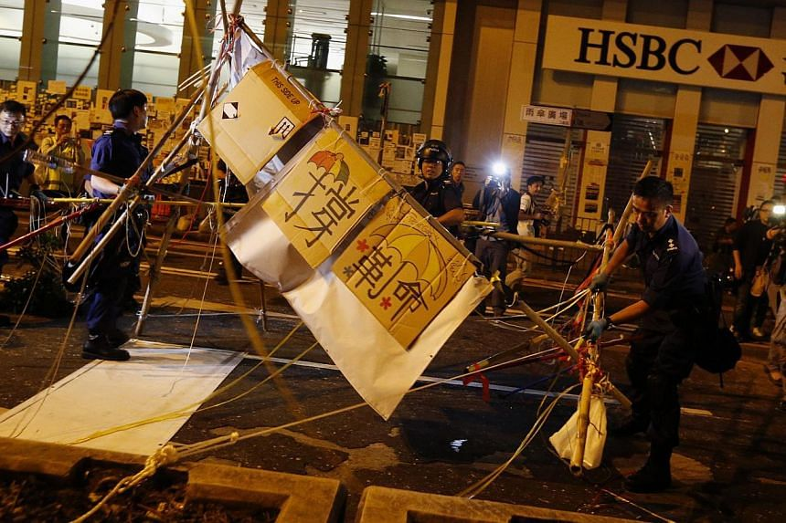 Police demolish a barricade outside a HSBC branch on a road blocked by pro-democracy protesters at the Mong Kok shopping district in Hong Kong, on Oct 17, 2014. -- PHOTO: REUTERS