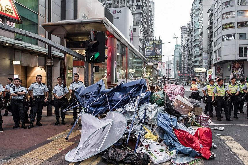 Police forces stand next to what is left of an encampment of pro-demoracy protesters in the Mong Kok district of Hong Kong, on Oct 17, 2014. -- PHOTO: AFP