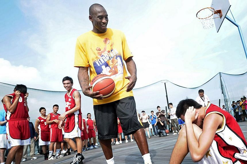 More than 60 young people had the opportunity of a lifetime at the Marina Bay Sands SkyPark on Sept 17, 2011 – sharing a basketball court with Los Angeles Lakers superstar Kobe Bryant (standing, with ball). -- PHOTO: ST FILE