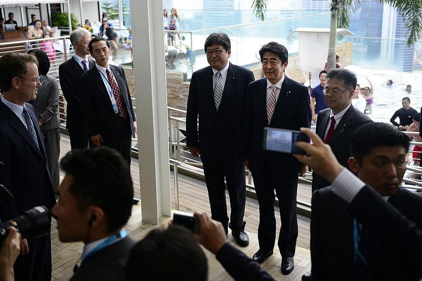 Japanese Prime Minister Shinzo Abe (third from right) touring the Marina Bay Sands integrated resort on May 30, 2014, accompanied by chief executive officer George Tanasijevich (left). -- PHOTO: ST FILE