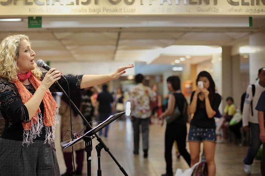 Ms Kimberly Creasman singing parodies of classic Disney songs along the hallways of the Singapore General Hospital as part of the inaugural MusicFest@SGH on 21 June 2013. -- PHOTO: ST FILE