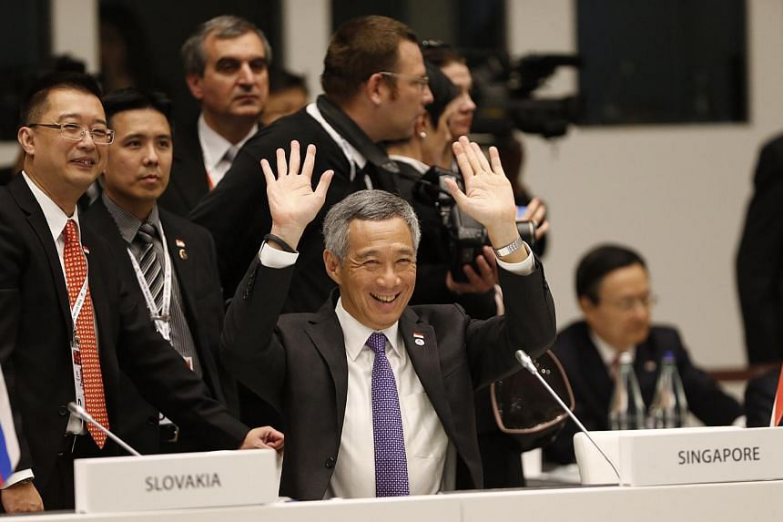 PM Lee Hsien Loong - seen with Ministry of Foreign Affairs deputy secretary Simon Wong (far left) - waving to fellow Asian and European leaders at the opening ceremony of the Asia-Europe Meeting in Milan yesterday.