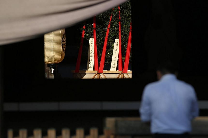 "A wooden sign (left) which reads ""Prime Minister Shinzo Abe"" is seen on a ritual offering, a masakaki tree, from the prime minister to the Yasukuni Shrine, inside the main shrine as a visitor prays at the front shrine in Tokyo, Japan on Oct 17, 2014."