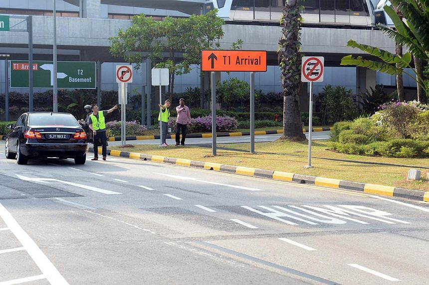 Traffic wardens directing motorists to park at the multi-storey carpark at Terminal 2. -- ST PHOTO: AZIZ HUSSIN