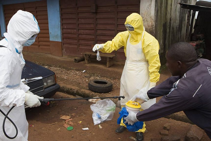 Health workers in protective equipment handle a sample taken from the body of someone who is suspected to have died from Ebola virus, near Rokupa Hospital, Freetown on Oct 6, 2014. -- PHOTO: REUTERS