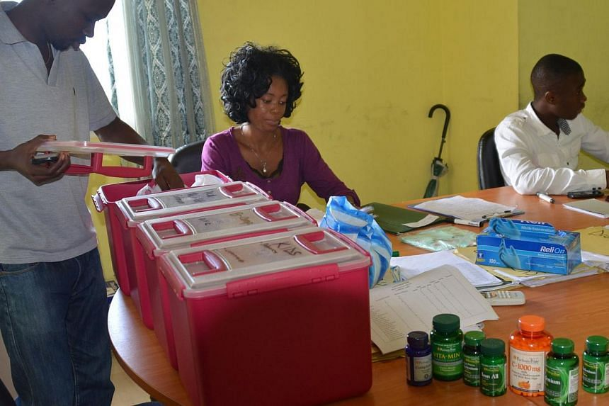 Members of the NGO U Fondation prepare medication on Oct 16, 2014 in Monrovia, before visiting quarantined people suffering from the Ebola virus. -- PHOTO: AFP
