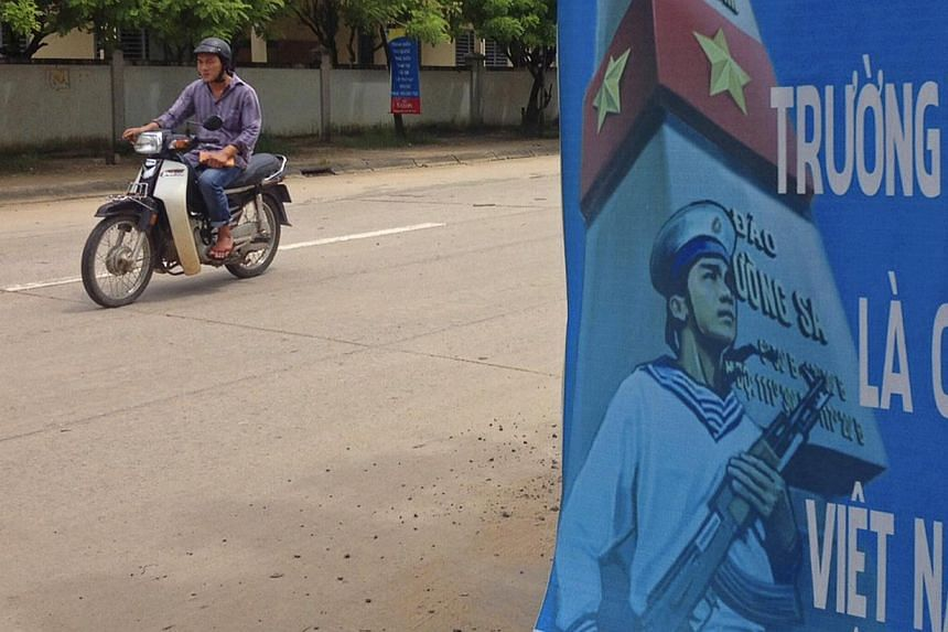 """A man riding a motorcycle past a poster promoting Vietnam' sovereignty in what is calls the East Sea (also known as the South China Sea) on Phu Quoc island Sept 11, 2014. The poster reads: """"Paracel Islands, Spratly Islands belong to Vietnam"""". -- PHOT"""