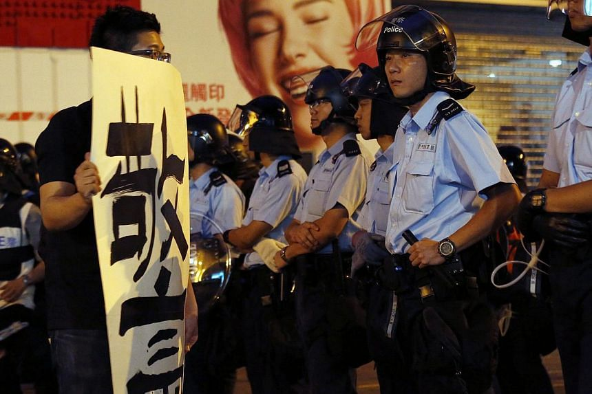 """A pro-democracy protester carrying a banner which reads """"black cop"""" in front of a line of policemen off a road blocked by pro-democracy protesters at Mongkok shopping district in Hong Kong on early October 17, 2014. -- PHOTO: REUTERS"""