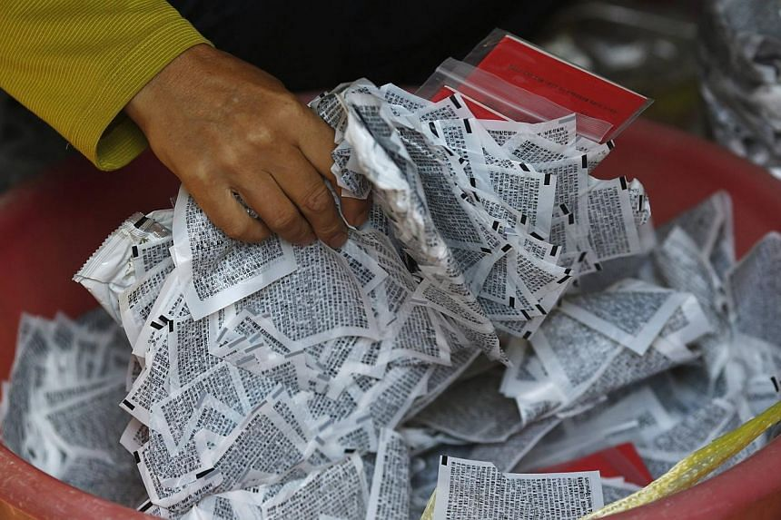 North Korean defector Lee Min Bok picking up leaflets condemning North Korean dictatorship at his home in Pocheon, about 15km south of the demilitarized zone separating the two Koreas, October 15, 2014. It's only propaganda, but the leaflets infuriat