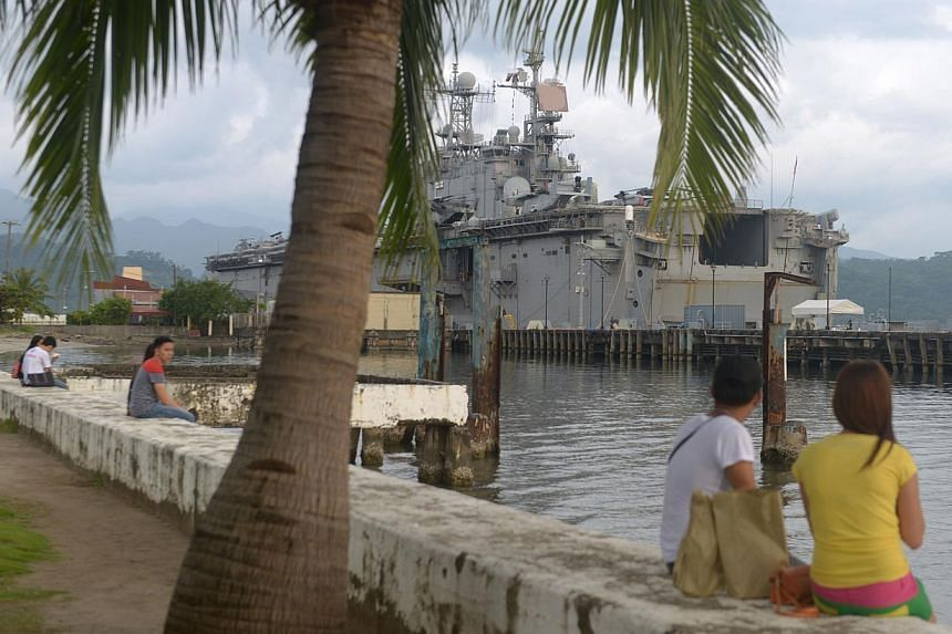 Students looking on alongside the USS Peleliu in the northern Philippine port city of Olongapo on Octobar 14, 2014. The two ships were in the Philippines for just-concluded joint amphibious opeation exercises. However the USS Peleliu may be staying l