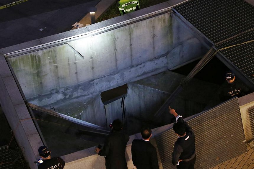 Police officials examine the scene of an accident at a shopping district in Seongnam on Oct 17, 2014. -- PHOTO: REUTERS