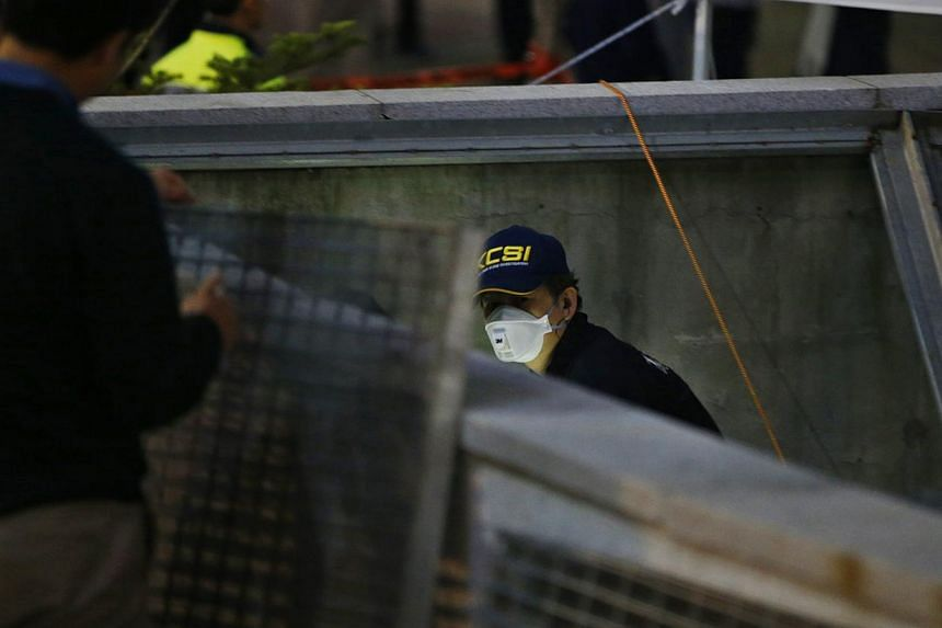 A police official examines the scene of an accident at a shopping district in Seongnam on Oct 17, 2014. -- PHOTO: REUTERS