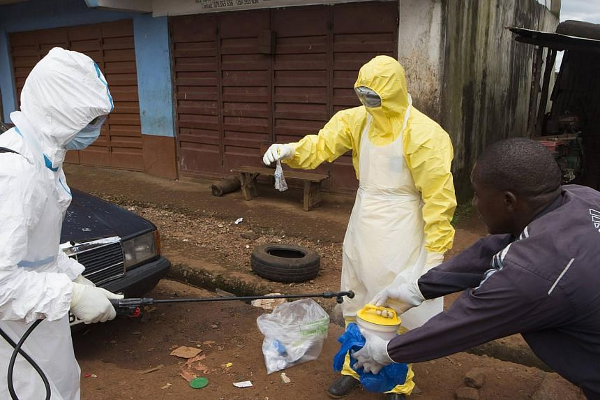 Health workers in protective equipment handle a sample taken from the body of someone who is suspected to have died from Ebola virus, near Rokupa Hospital, Freetown Oct 6, 2014.Ebola has killed at least two people in what was the last remaining