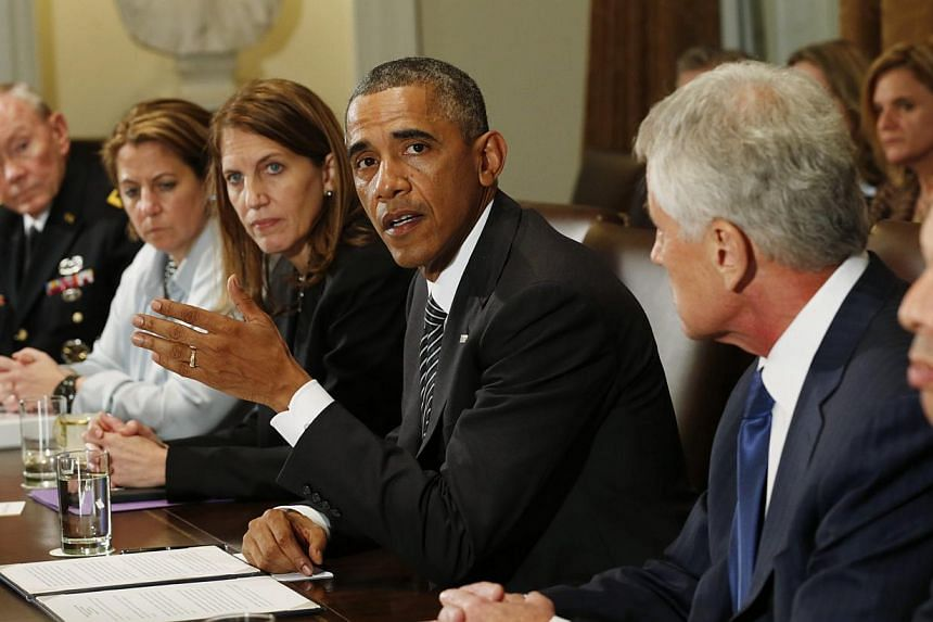 US President Barack Obama (middle) holds a meeting with cabinet agencies coordinating the government's Ebola response in the Cabinet Room of the White House in Washington on Oct 15, 2014. -- PHOTO: REUTERS