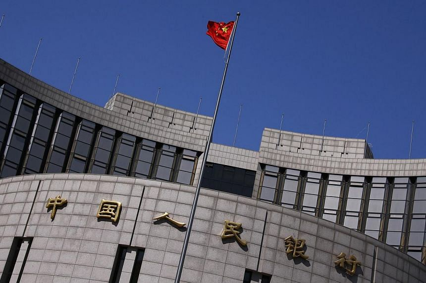 A Chinese national flag flutters outside the headquarters of the People's Bank of China, the Chinese central bank, in Beijing. -- PHOTO: REUTERS