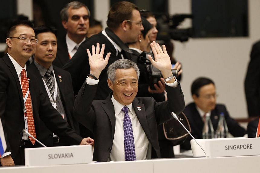 Prime Minister Lee Hsien Loong waves to fellow Asian and European leaders at the opening ceremony of the Asia-Europe Meeting (ASEM) summit in Milan on Thursday Oct 16. To Mr Lee's right (in glasses) is Ministry of Foreign Affairs deputy secretary Sim