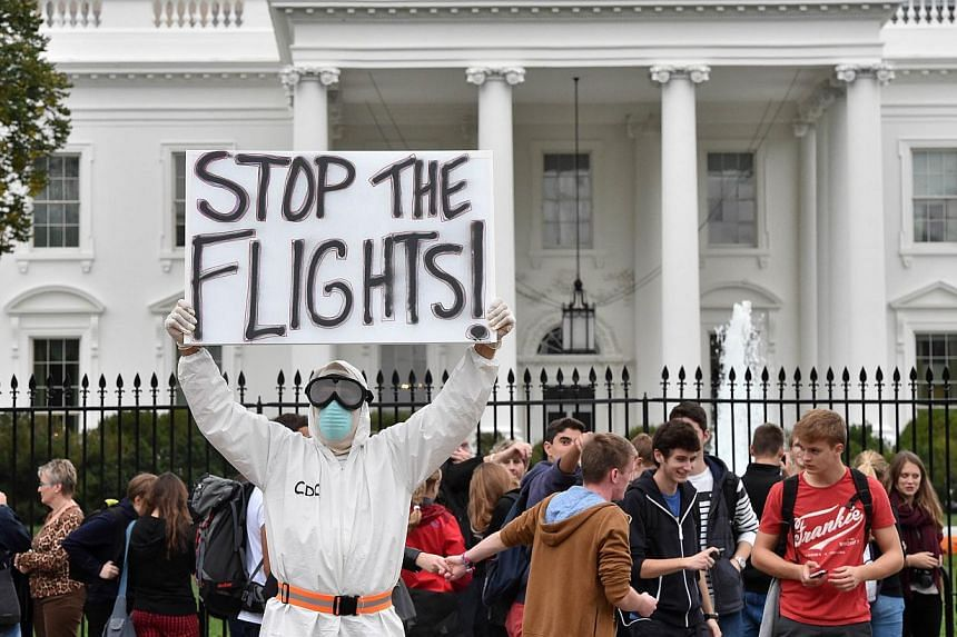 Jeff Hulbert from Annapolis, Maryland, dressed in a protective suit and mask, holds a poster demanding a halt to all flights from West Africa, as he protests outside the White House in Washington, DC on Oct 16, 2014. Top US health officials faced a g