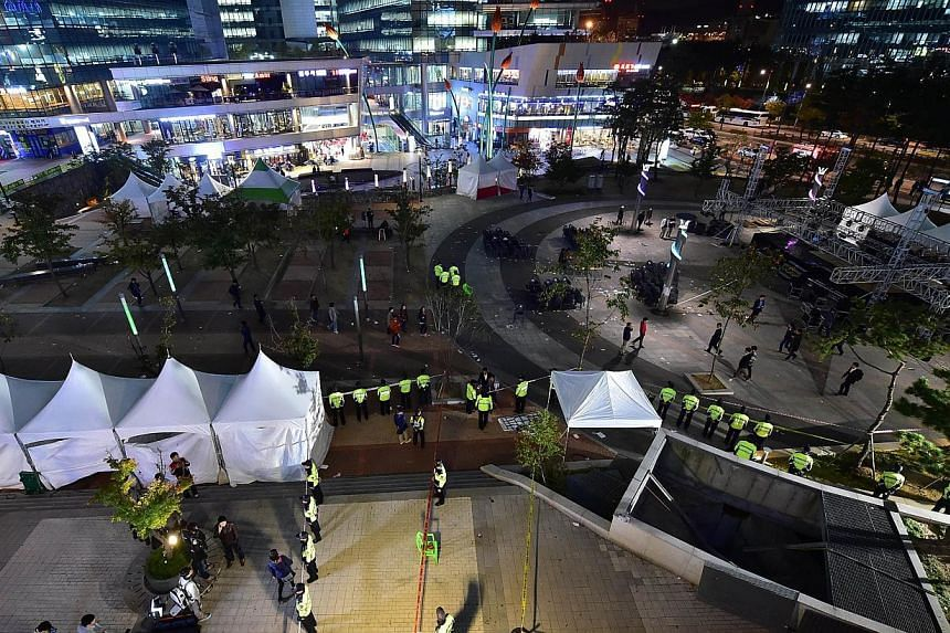 Policemen stand guard near a broken ventilation grate (bottom right) after concert goers fell through it into an underground parking area below in Seongnam City, south of Seoul on Oct 17, 2014. -- PHOTO: AFP
