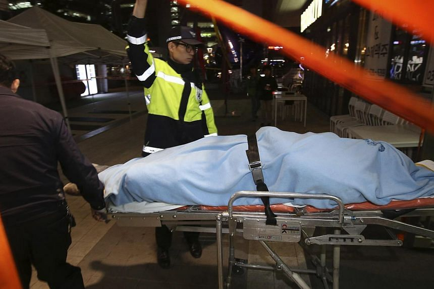 Firefighters carry an injured person on a stretcher at a shopping district in Seongnam on Oct 17, 2014. -- PHOTO: REUTERS