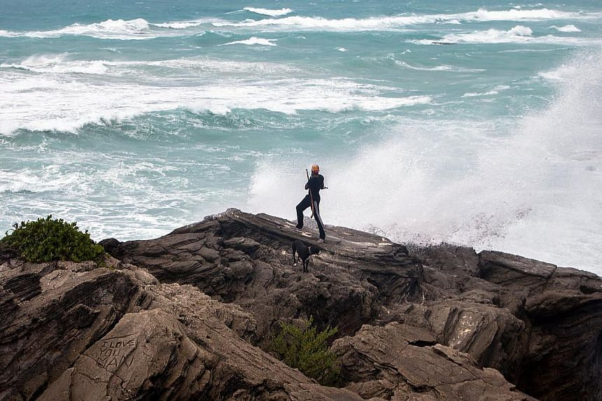 A man takes photos while standing on a cliff on the island's south shore as it is battered by winds from approaching Hurricane Gonzalo, in Astwood Park, Oct 17, 2014. -- PHOTO: REUTERS