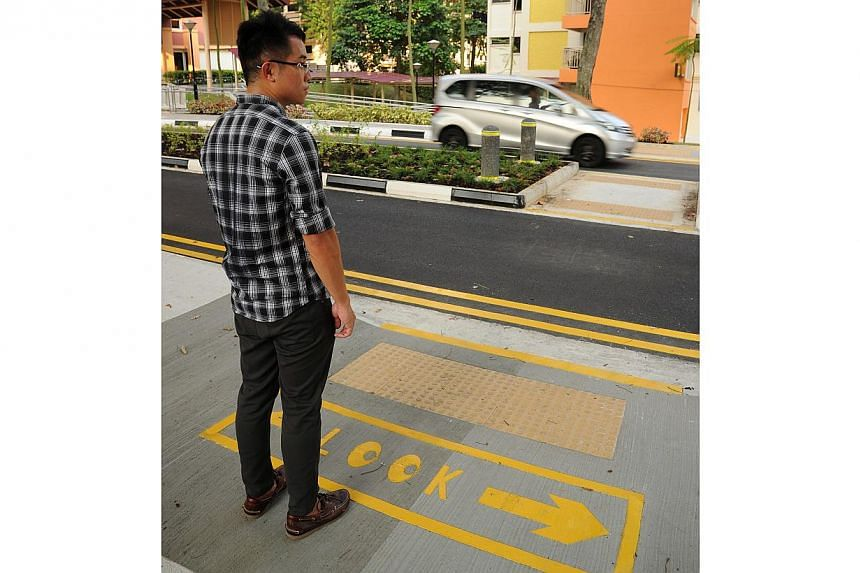 """Eye-land - two-stage crossing with yellow """"LOOK"""" markings, bold yellow line at ramp downs, bollards with highly reflective sheeting, and homogeneous tactile tiles.-- PHOTO:LAND TRANSPORT AUTHORITY"""