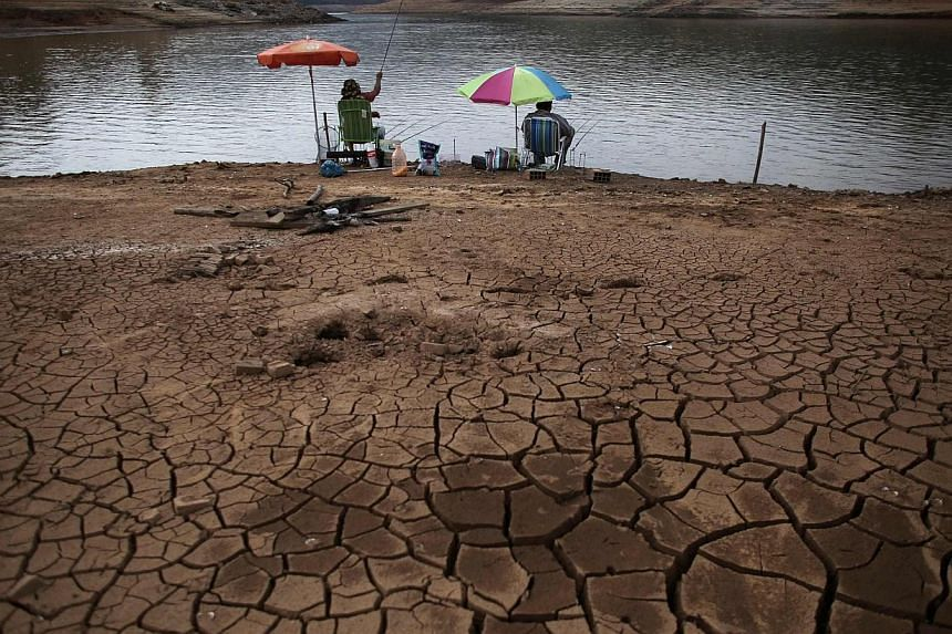 Men fish next to cracked ground as the Atibainha dam lake dries up due to a prolonged drought in Nazare Paulista, Sao Paulo state, on Oct 17, 2014. -- PHOTO: REUTERS