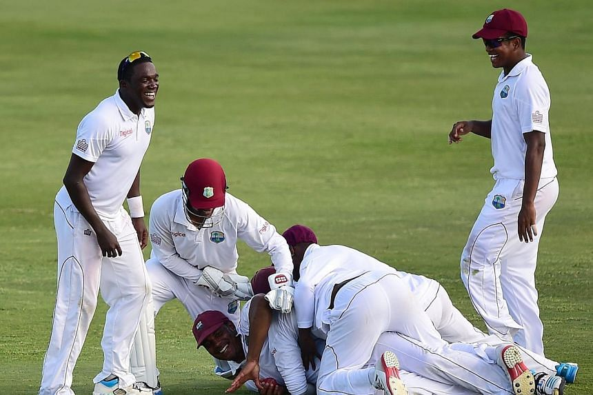 Shannon Gabriel of the West Indies is mobbed by teammates after catching out Mominul Haque of Bangladesh off a delivery from bowler Sulieman Benn on day four of the second and final Test between West Indies and Bangladesh on Sept 16, 2014. The West I