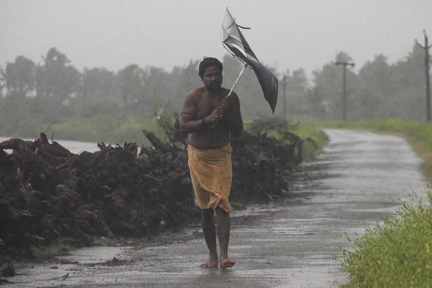 A man struggles with an umbrella in strong winds and rain caused by Cyclone Hudhud in Gopalpur in Ganjam district in the eastern Indian state of Odisha on Oct 12, 2014.The death toll from a cyclone that hit India's east coast last week ha